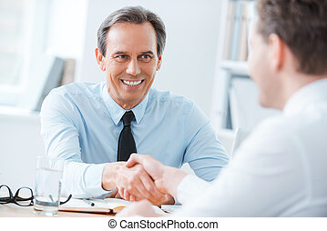 Sealing a deal. Two business people shaking hands while...