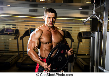 Handsome muscular man in the gym. Weightlifter with the...