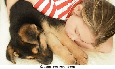 little girl hugging a puppy sleepin