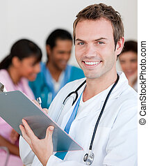 Young male Doctor Smiling at the camera with his team in teh...