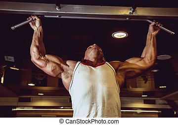 Handsome muscular man in gym making elevations. Bodybuilder...