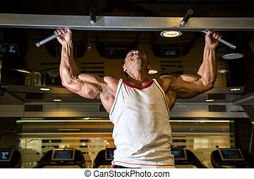 Muscle athlete man in gym making elevations. Bodybuilder...