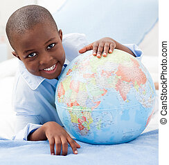 Boy looking at a globe while smiling at the camera - Young...