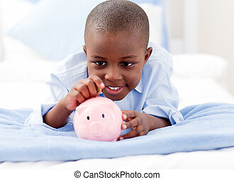 Young Boy on a bed putting money into a piggy bank - Young...