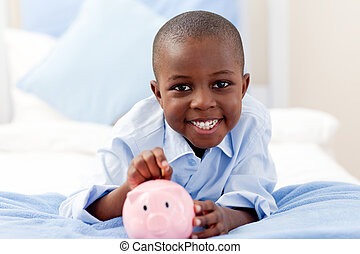 Young boy smiling at the camera while putting money into his...