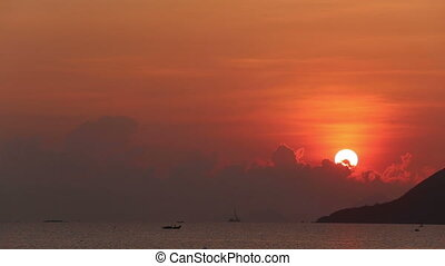 view of sunrise from behind clouds at beach of city resort -...