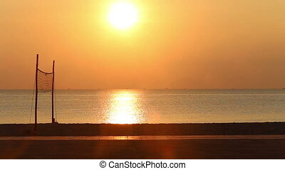 view of sunrise above beach with volleyball net - panorama...