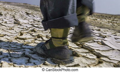 Feet Of Scientist Walking On Cracked Desert Earth - Low...