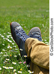 Feet in shoes on green field with flowers