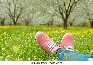 Feet in pink shoes on green field with flowers