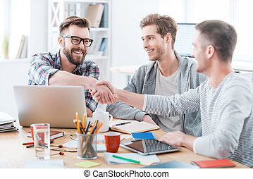 Sealing a deal. Business people shaking hands while sitting...