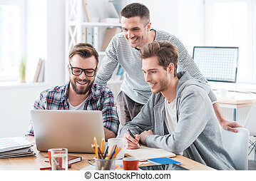 Solving problems as one team. Three cheerful young men working together while sitting at their working place in office