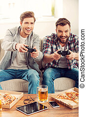 We love this game Two cheerful young men playing video games...