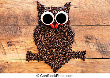 Coffee owl. Top view of funny owl made from coffee beans laying on the wooden desk