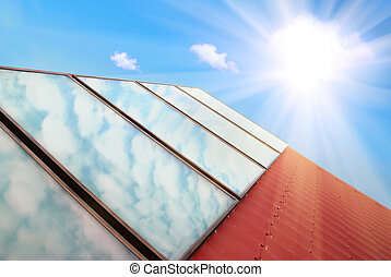 Solar system - Solar panels on the red house roof with blue...