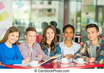 Teenagers - A group of teenagers sitting at the table in...