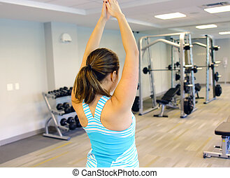 Sporty woman stretching her arm, in a gym.