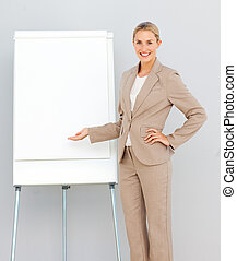 Businesswoman Standing  pointing at a whiteboard and smiling