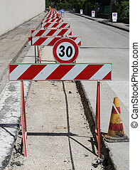 speed limit sign and hurdles in the road excavation