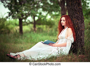 Cute red-haired woman sitting under tree and reading a book...