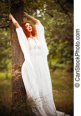 Charming redhead woman wearing white dress stands near tree...