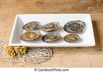 Raw limpets, rustic background