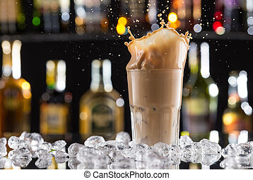 Cold coffee drink with ice, beans and splash