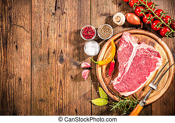 Raw fresh meat t-bone steak and seasoning on wooden...