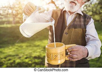Farmer with milk jug - Senior farmer with milk in a glass...