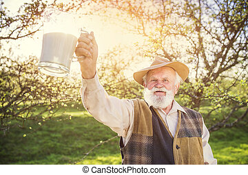 Farmer with milk jug - Senior farmer with milk in a glass...