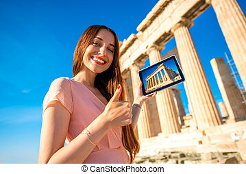 Woman advertising Acropolis with digital tablet near...