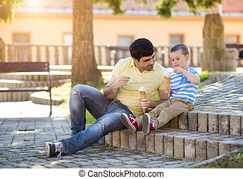 Father and son enjoying icecream outside in a park