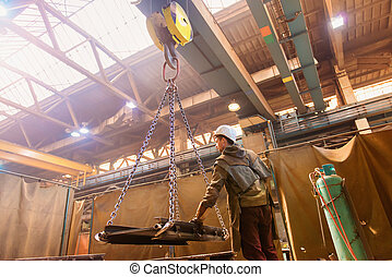 Man welding - Young man in a factory preparing equipment for...