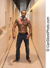 Mature Man Listening Music In Modern Corridor - Muscular...