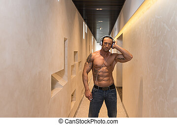 Mature Man Listening Music In Modern Corridor - Muscular...