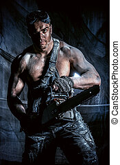 sawmill - Handsome muscular man with a chainsaw over dark...