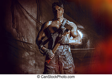smithy - Handsome muscular coal miner with a hammer over...