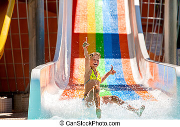 Child on water slide at aquapark. - Happy child girl in...