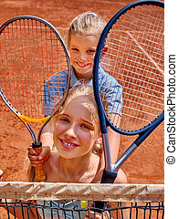 Two sister girl athlete with racket and ball on brown tennis...