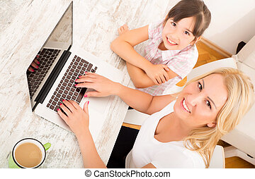 Mother and Daughter with a Laptop at home - A mother with...