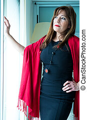 Beautiful mature woman looking out of the window - A...