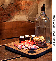 Vodka and bacon, tomato and bread on wooden table