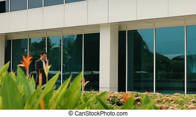Businessman Chatting On Mobile Phone Walking To Office -...