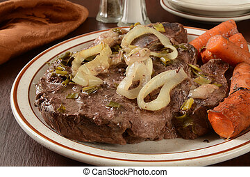 Pot roast - Juicy pot roast on a platter with carrots and...
