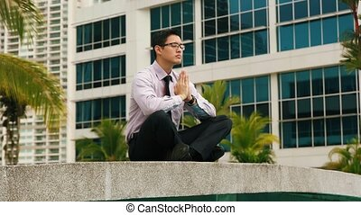 Chinese Businessman Meditating Yoga Outside Office During...
