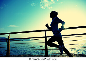 healthy lifestyle sports woman running on wooden boardwalk...