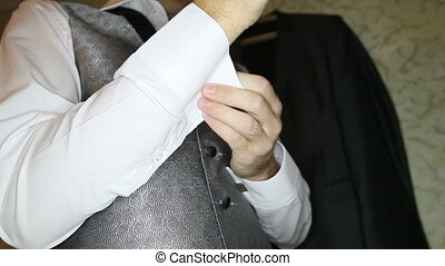 groom in silver vest puts on cufflinks on white shirt -...