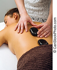 Massage therapist placing the hot stones - Photo of a young...