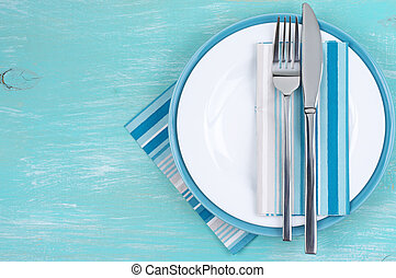 Table setting: white plate, fork and knife with napkins on...