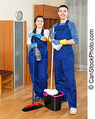 Two smiling cleaners cleaning floor